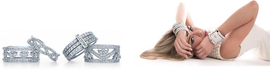 A woman wearing diamond bracelets laying next to four diamond rings