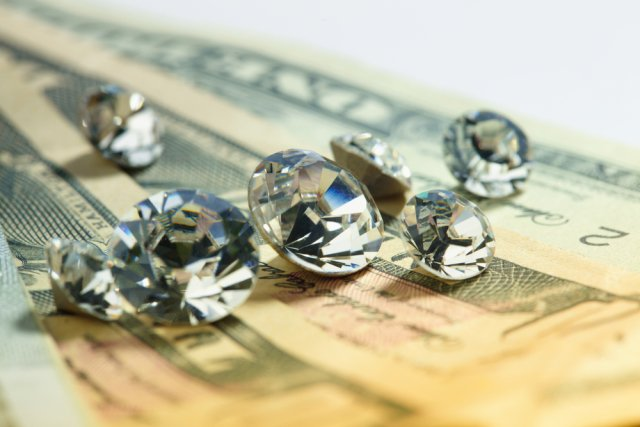 Seven loose diamonds of varying sizes on top of money