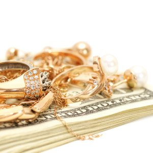 A variety of gold jewelry pieces on top of a stack of one hundred dollar bills